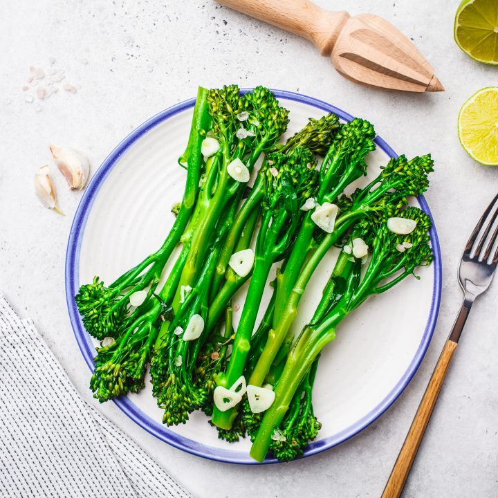 Boiled broccolini with garlic white plate