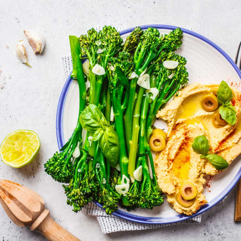 Cooked broccolini with hummus white plate top view