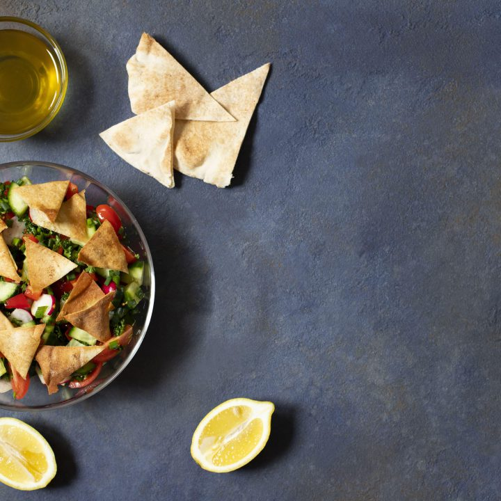 Traditional fattoush salad with vegetables pita bread levantine arabic middle eastern cuisine served glass plate with lemon pita olive oil dark background top view space text min