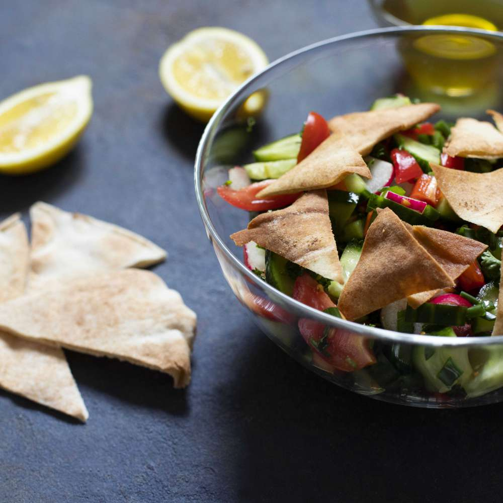 Traditional fattoush salad with vegetables pita bread levantine arabic middle eastern cuisine served glass plate with lemon pita olive oil dark background close up min