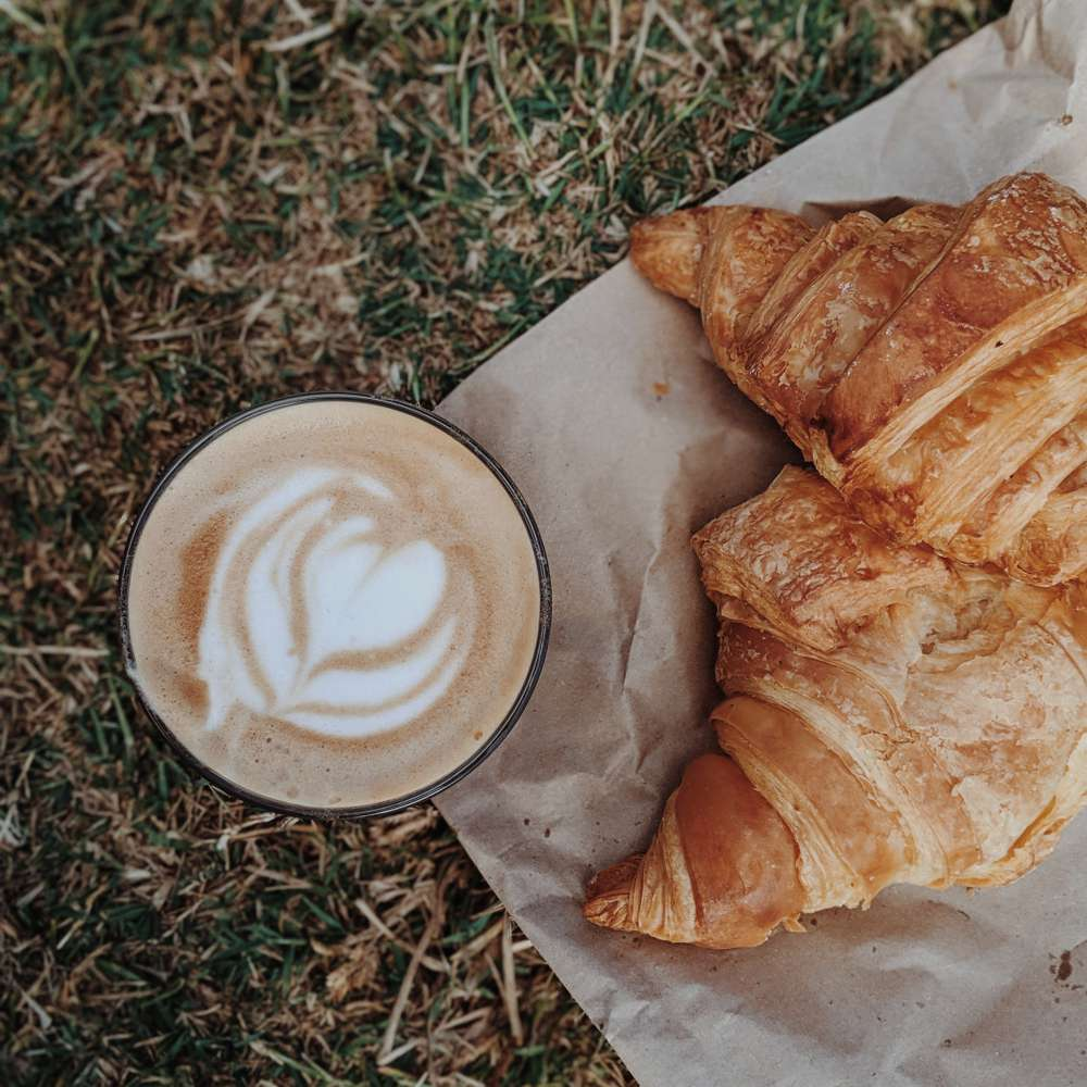 Cappuccino by croissant on ground 2974486