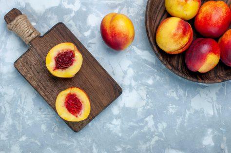 Top view fresh peaches mellow tasty fruits inside brown plate light white desk min