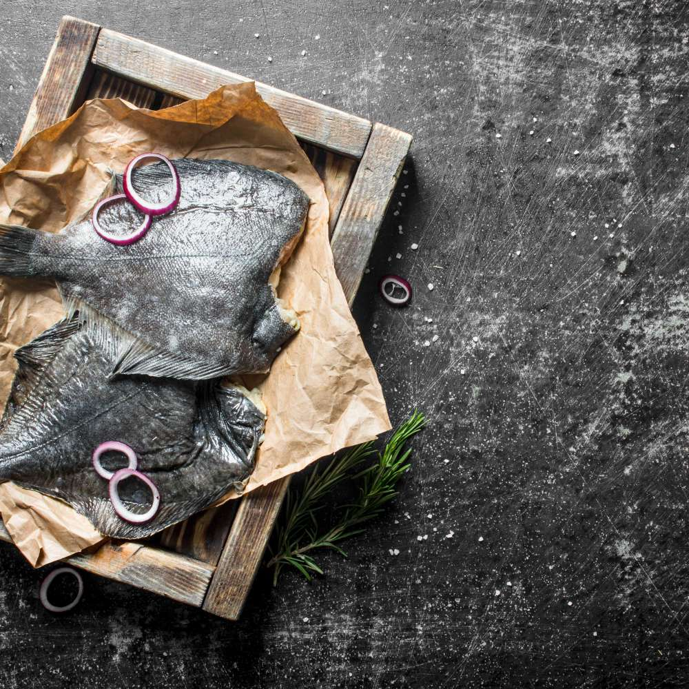 Raw fish flounder tray with onion rings garlic cloves dark rustic background min