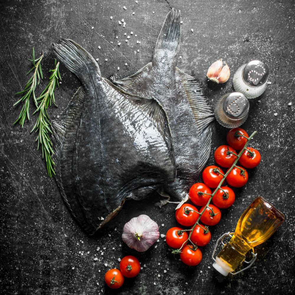 Raw fish flounder with cherry tomatoes spices garlic dark rustic min