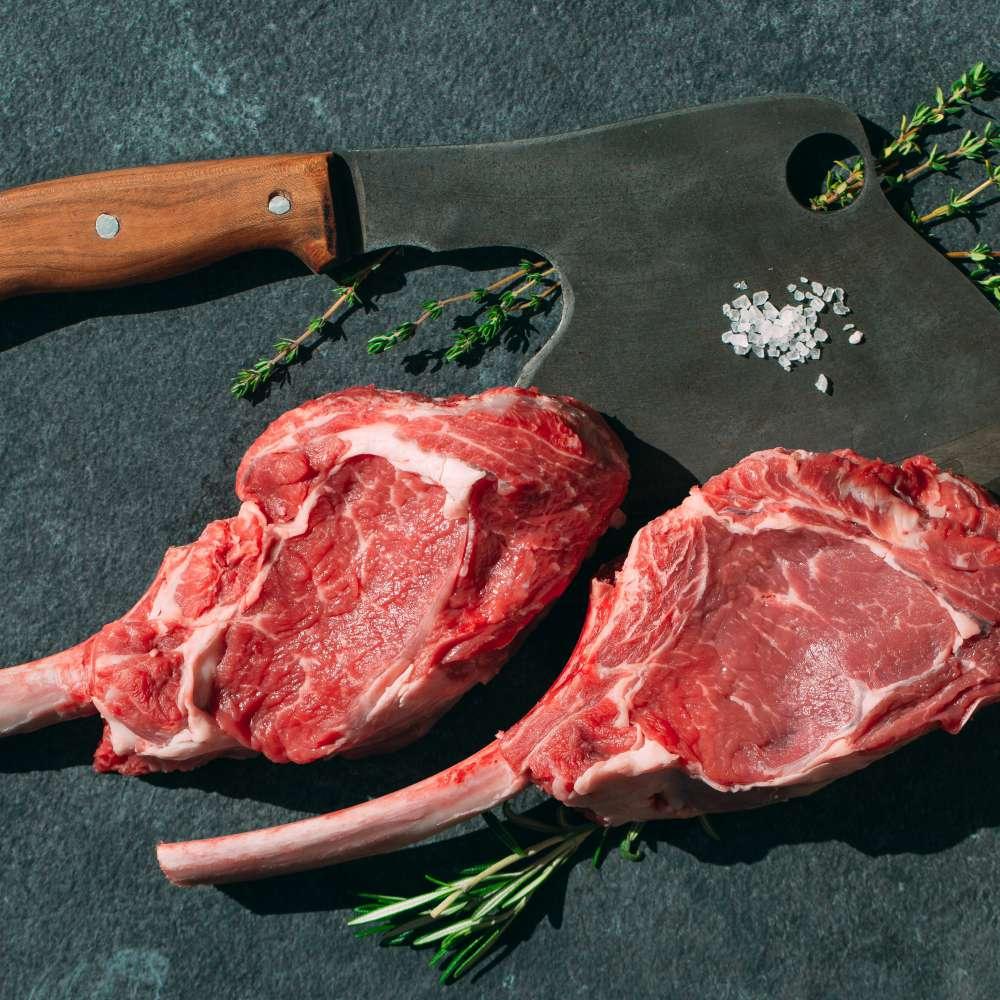 Raw steak with meat cleaver dark stone