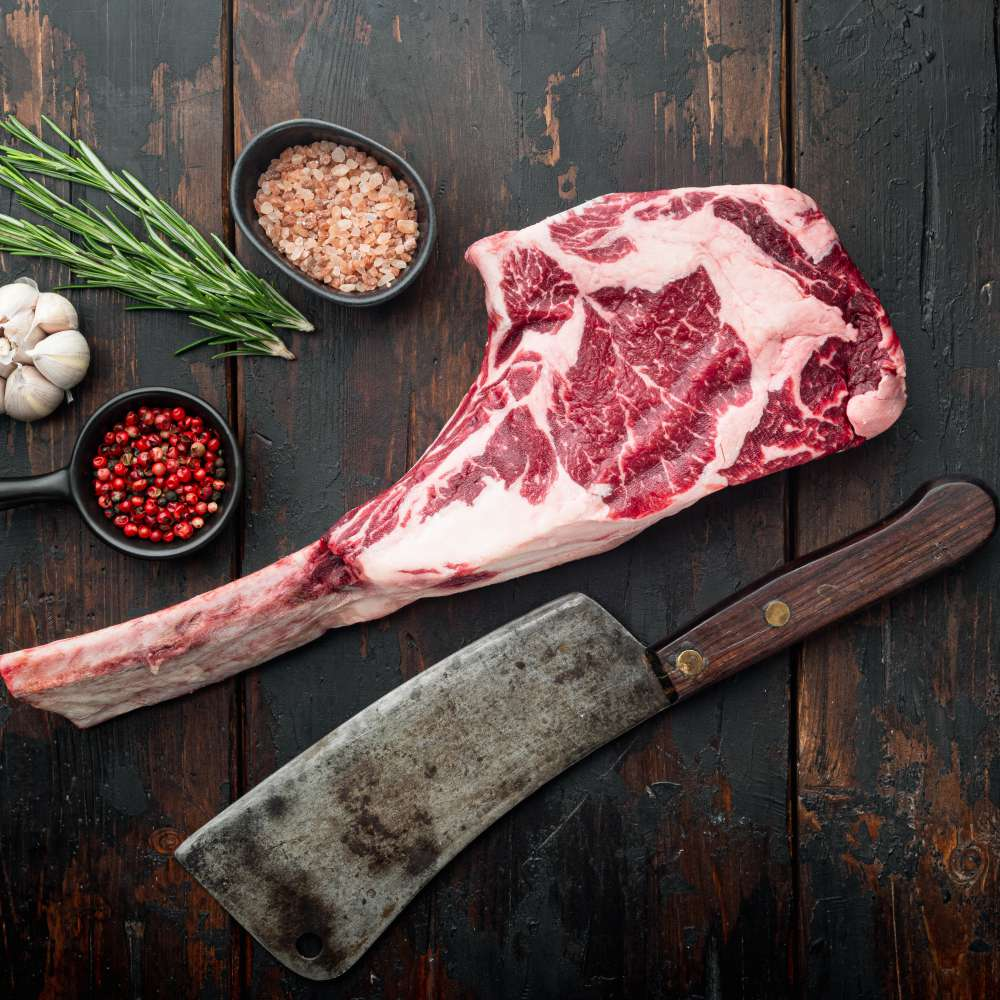 Raw uncooked black angus beef tomahawk steak bone set old butcher cleaver knife with seasoning herbs old dark wooden table