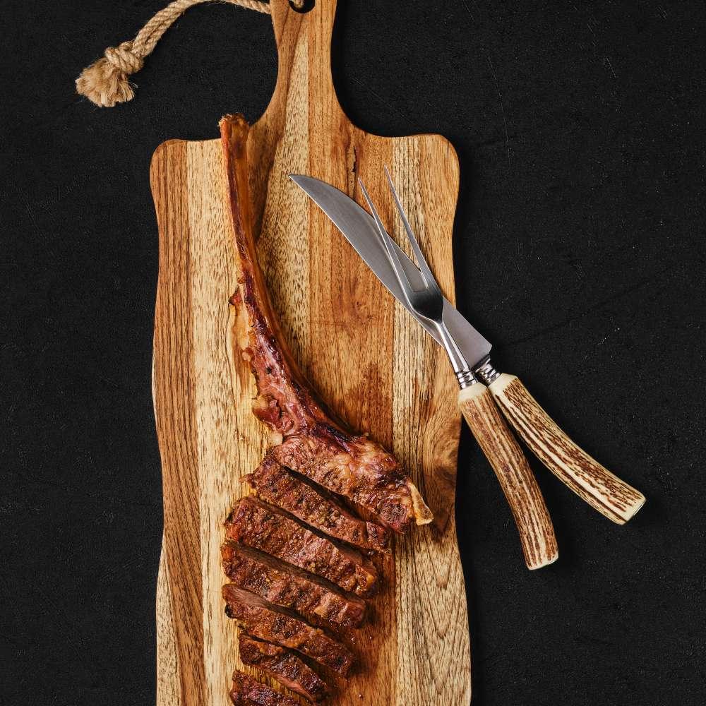 Tomahawk steak cut slices wooden board min
